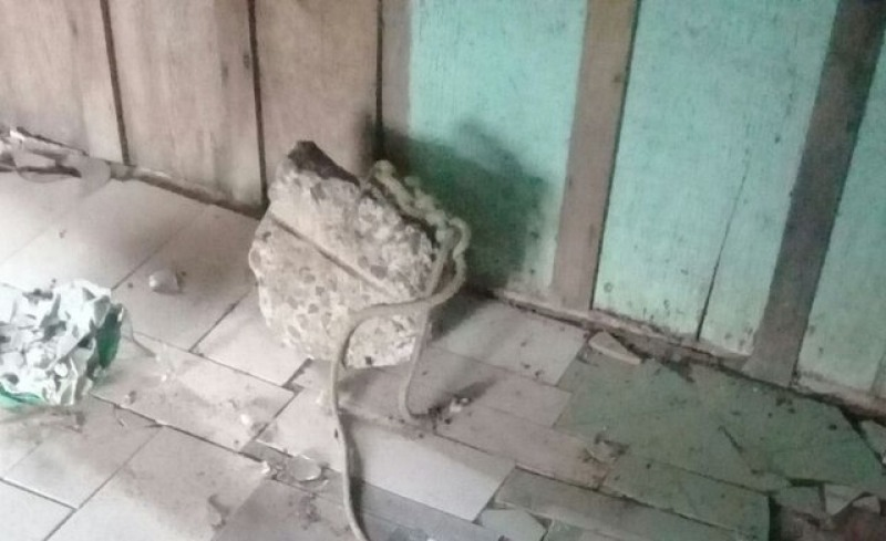 Pedra com uma corda amarrada nela foi encontrada no interior da casa (Foto: Assessoria PM)